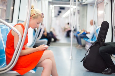 29558384 - beautiful blonde caucasian lady in red dress traveling by metro