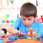 21538107 - cute little boy moulds from plasticine on table