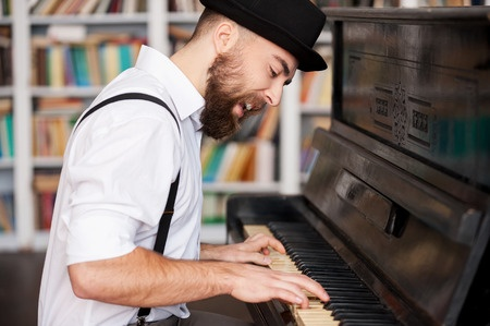 26366771 - he got creative soul. handsome young bearded men playing piano and singing
