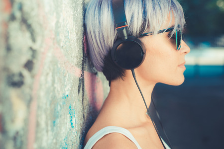 31657436 - young beautiful short blue hair hipster woman with headphones music in the city