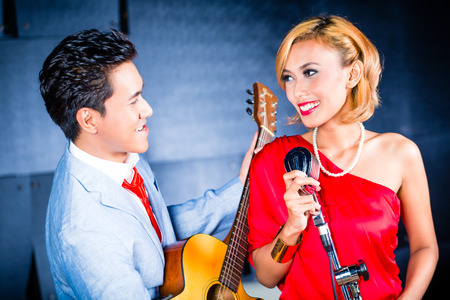 33724947 - asian professional singer and guitarist recording new song or album cd in studio