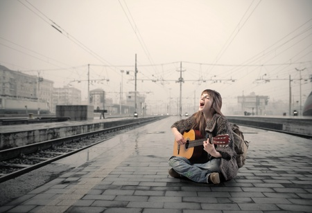 8612306 - young woman singing and playing guitar on the platform of a train station