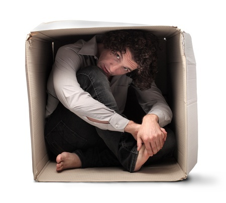 15662604 - man crouched in a box holding one of his feet