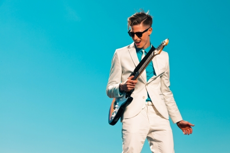 19879559 - retro fifties male electric guitar player wearing white suit and sunglasses