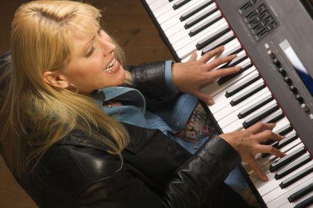 2673693 - femal musician sings while playing digital piano