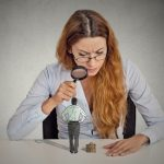 35516173 - curious corporate businesswoman skeptically meeting looking at small employee standing on table through magnifying glass isolated grey office wall background. human face expression attitude perception