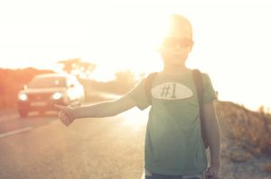 45589868 - little child hitchhiking alone summer sunset background