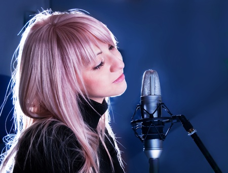 10001686 - the portrait of beautiful blondie with microphone on blue background