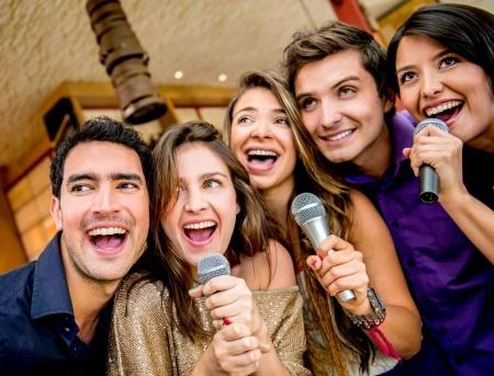 19400175 - happy group of people karaoke singing at the bar