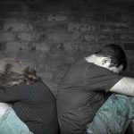 27085304 - divorce,problems - young couple angry at each other sitting back to back with a bricks wall background