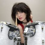 3740974 - beautiful teen girl in red vinyl dress and dog collar sitting at drum set.