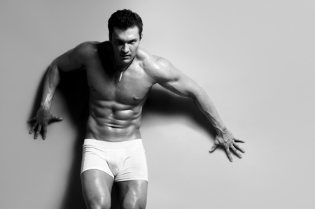 11219962 - the very muscular handsome sexy guy on grey background, strict