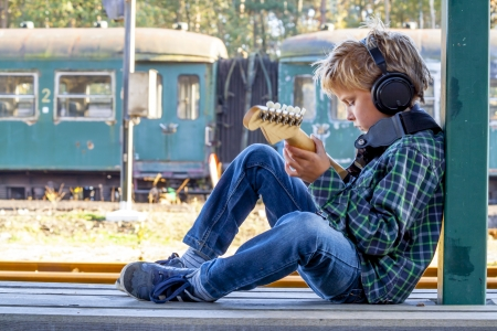 18628286 - kid playing guitar at old railroad station
