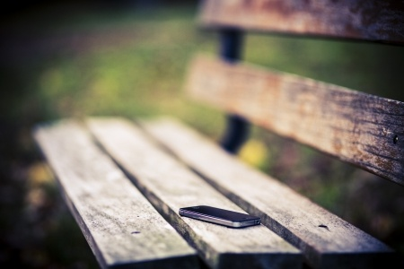 23544844 - someone forgot cell phone on a bench in the park
