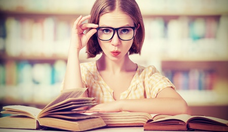 26519495 - funny crazy girl student with glasses reading books in the library