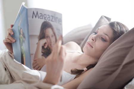 28862053 - woman lying in bed while reading a magazine