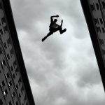 37963179 - man jumping over building roof against gray sky background