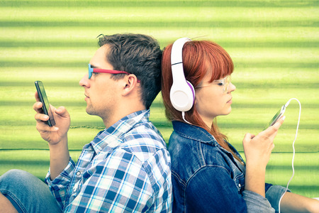 39540910 - hipster couple in disinterest moment with mobile phones - concept of apathy sadness and isolation using new technologies - boyfriend and girlfriend with smartphones addiction - vintage filtered look