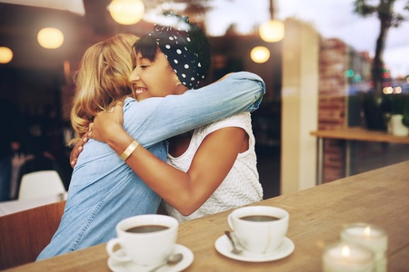 46626119 - two multi ethnic affectionate girl friends embracing as they sit in a coffee shop enjoying a cup of coffee together