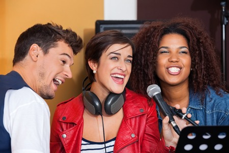 47828134 - happy male and female band members singing in recording studio