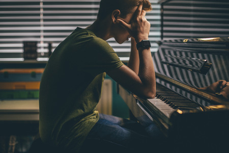 65204955 - teenager sitting at his piano with his head in his hands.