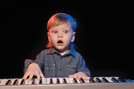 14153582 - playing and singing little boy on black background