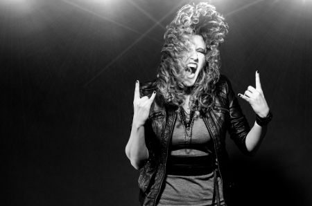 22105115 - ecstatic woman is dancing to the rock music