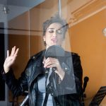46945178 - young female singer seen through glass in recording studio