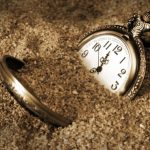 10507416 - a pocket watch is buried in the dirty sand.