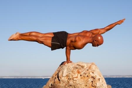 14738444 - balance strong man balancing on rock.