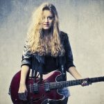 15264032 - blonde girl playing electric guitar
