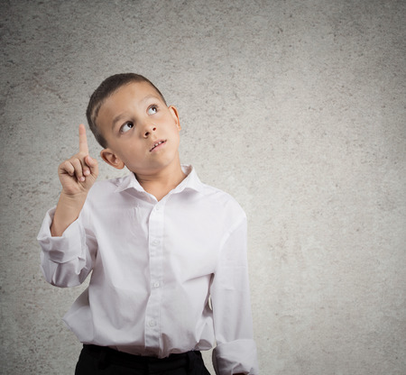 31063334 - child thinking. boy looking, pointing up, has idea, solution, isolated grey wall background with copy space to right. face expressions, human emotion, body language, life perception. education concept