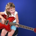 3453283 - little girl playing with red electric guitar and singing