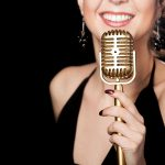 36301138 - elegant young female singer in black dress smiling holding golden vintage microphone, live performance, concert, unrecognizable person, close up, focus on mic, copy space