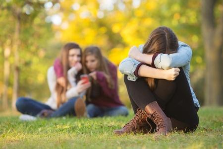 37674108 - sad teenage woman sitting with head down near laughing group