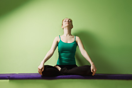 41031702 - redhead caucasian woman breathing while sitting in lotus yoga pose at the green wall