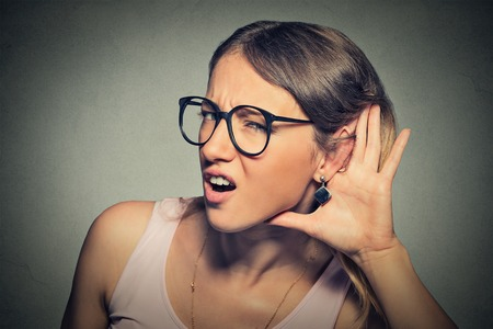 42814125 - closeup portrait young nosy woman hand to ear gesture trying carefully intently secretly listen in on juicy gossip conversation news isolated gray background.