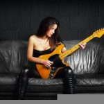 21383380 - photo of a sexy female guitar player wearing leather boots and sitting on old leather couch.
