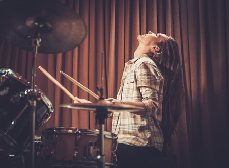 43842126 - young cheerful girl behind drums on a rehearsal