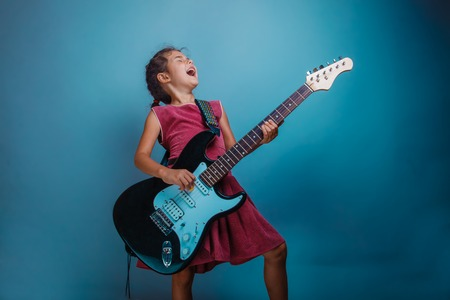 44118680 - teenage girl playing electric guitar studio background photo stands sideways shouts sings
