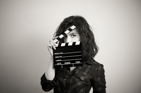 55561346 - woman actress eyes portrait behind movie clapper board vintage black and white