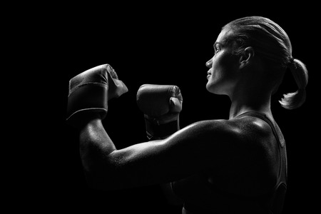 57683434 - side view of female boxer with fighting stance against black background
