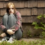 5907015 - a teenage girl with a sad expression sits against a run-down house.