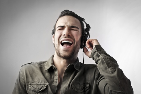 12647442 - young man singing while listening to music