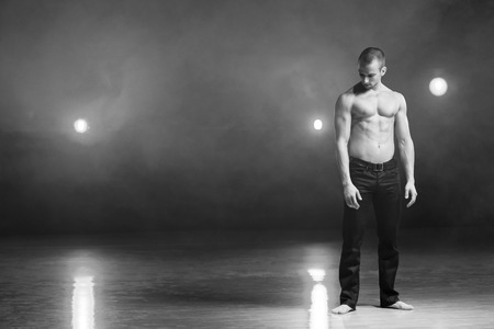 28498570 - young and muscular man performing a contemporary dance pose on a stage a black and white image with grain added as effect